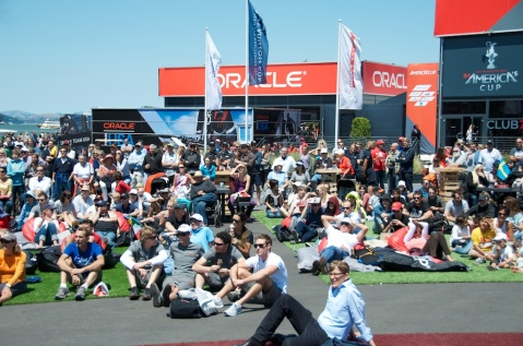 Spectators enjoy the great weather and watch the racing on the big screen