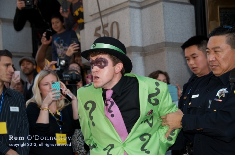 The Riddler is taken away by police after Batkid and Batman catch him in a bank vault.